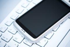 Téléphone intelligent sur l'ordinateur portatif Photos libres de droits