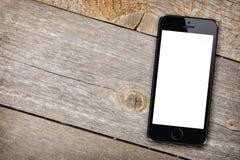 Téléphone intelligent sur la table en bois Image stock