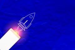 Téléphone intelligent sur le fond de papier bleu avec l'espace et la fusée de copie Photo libre de droits
