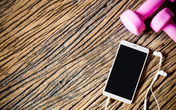 Téléphone intelligent vide de Moblie avec le téléphone d'oreille et les haltères sur le bois, h Images stock