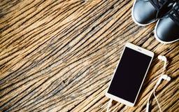 Téléphone intelligent vide de Moblie avec le téléphone et les espadrilles d'oreille sur le bois, à Image libre de droits
