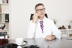 Téléphone masculin de Calling Client Through de médecin photo libre de droits