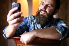 Téléphone modifié la tonalité barbu de regard d'homme photographie stock libre de droits