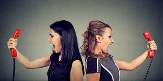 téléphone noir de récepteur de concept de transmission Deux femmes fâchées criant à l'un l'autre au-dessus du téléphone photo libre de droits
