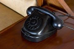 Téléphone noir poussiéreux de vieux vintage de disque sur le bureau photos stock