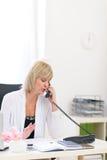 Téléphone parlant aîné de femme d'affaires Images libres de droits