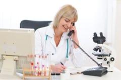 Téléphone parlant de femme aînée de docteur au bureau Photographie stock libre de droits