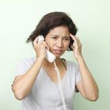 Téléphone parlant de femme avec la main sur la tête photographie stock