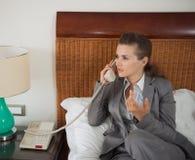Téléphone parlant de femme d'affaires dans la chambre d'hôtel Photographie stock