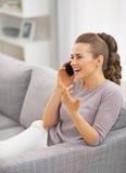 Téléphone parlant de femme heureuse dans le salon image libre de droits