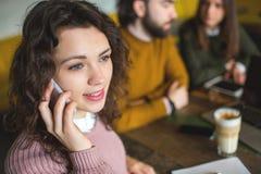 Téléphone parlant de jeune femme avec les amis heureux en café Photo libre de droits