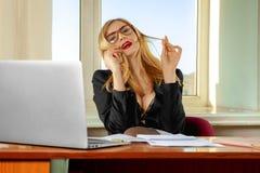 Téléphone parlant de secrétaire d'une forte poitrine à la mode dans le bureau Images libres de droits