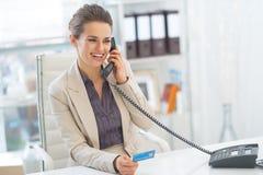 Téléphone parlant de sourire de femme d'affaires dans le bureau Photographie stock