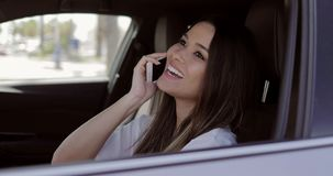 Téléphone parlant de sourire de modèle dans la voiture banque de vidéos