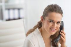 Téléphone parlant moderne de femme d'affaires dans le bureau Photographie stock