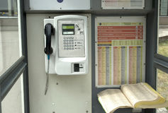 Téléphone payant avec le téléphone et le livre Photographie stock