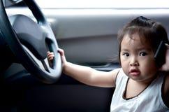 Téléphone portable asiatique d'utilisation de bébé dans la voiture Photographie stock libre de droits