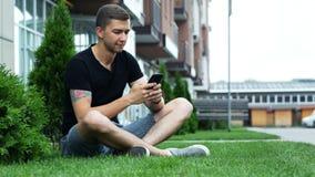 Téléphone portable attrayant d'utilisation d'homme tout en se reposant sur l'herbe près de l'hôtel, causant avec des amis clips vidéos