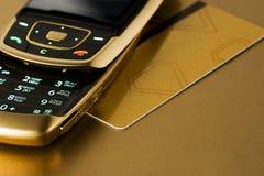 Téléphone portable avec de l'or par la carte de crédit image stock