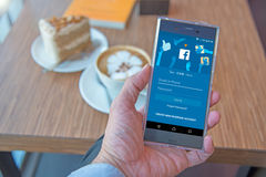 Téléphone portable avec l'écran de login d'application de Facebook et une tasse de café Photographie stock