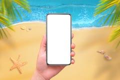 Téléphone portable avec l'écran isplated pour la maquette chez la main de la femme Plage et mer à l'arrière-plan Image stock