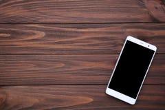 Téléphone portable avec l'écran vide sur le fond en bois brun Smartphone sur le Tableau en bois photographie stock libre de droits