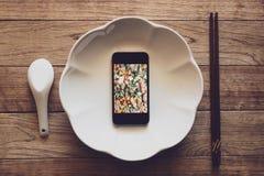 Téléphone portable avec l'image de nourriture sur l'écran dans un plat sur la table en bois avec les baguettes et la cuillère photos stock
