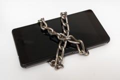 Téléphone portable avec la chaîne en métal verrouillée sur le blanc images stock