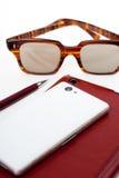 Téléphone portable avec la composition simple en lunettes de soleil Photos libres de droits