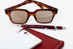 Téléphone portable avec la composition simple en lunettes de soleil Images stock