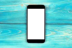 Téléphone portable avec la moquerie d'écran vide d'isolement sur le fond en bois bleu de table Smartphone sur le Tableau en bois  Photographie stock libre de droits