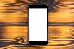 Téléphone portable avec la moquerie d'écran vide d'isolement sur le fond en bois brûlé de table Smartphone sur le Tableau en bois Images stock