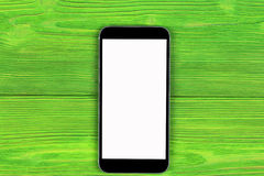 Téléphone portable avec la moquerie d'écran vide d'isolement sur le fond en bois vert de table Smartphone sur le Tableau en bois  Images stock
