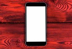 Téléphone portable avec la moquerie d'écran vide sur le fond en bois rouge de table Smartphone sur le Tableau en bois Écran de bl Image stock