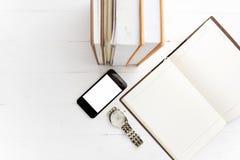 Téléphone portable avec la pile du livre et de la montre image stock