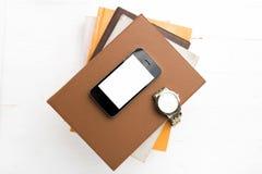 Téléphone portable avec la pile du livre et de la montre image libre de droits
