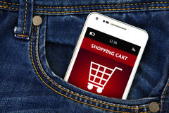 Téléphone portable avec le caddie dans la poche de jeans Photographie stock