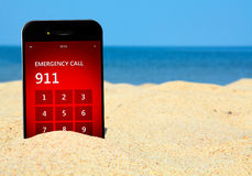Téléphone portable avec le numéro d'urgence 911 sur la plage Image stock