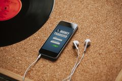 Téléphone portable avec le transfert d'argent APP dans l'écran et les écouteurs blancs sur un panneau de liège image libre de droits