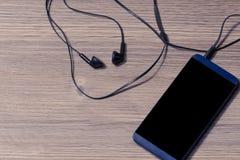 Téléphone portable avec les écouteurs noirs sur un concept futé de téléphone de smartphone de téléphone portable d'écouteurs de l photographie stock libre de droits