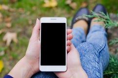 Téléphone portable blanc à disposition une jeune femme d'affaires de hippie sur le fond des feuilles naturelles vertes de buisson Photos libres de droits