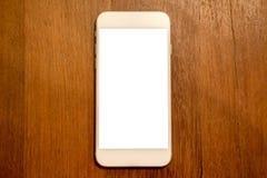 Téléphone portable blanc avec l'écran de bureau vide sur le fond en bois de table Photo libre de droits