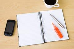 Téléphone portable, cahier et cuvette de café Photos libres de droits