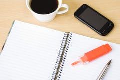 Téléphone portable, cahier et cuvette de café Photographie stock libre de droits