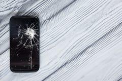 Téléphone portable cassé moderne sur le fond en bois blanc Copiez l'espace Vue supérieure Photos libres de droits