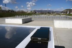 Téléphone portable chargeant à distance sur un banc solaire image libre de droits