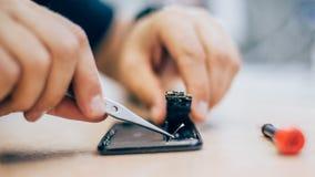 Téléphone portable défectueux de réparation de technicien dans le smartphone électronique t photo libre de droits