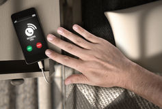 Téléphone portable d'appel d'arrivée à côté de lit Photo libre de droits