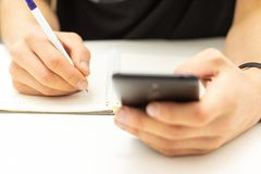 Téléphone portable d'utilisation d'étudiant recherchant l'information du réseau Inscription sur le cahier images stock