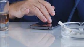 Téléphone portable d'utilisation de BusinessmMan fumant un cigare et buvant Alcoholan dans le bureau utilisant une portefeuille p photographie stock libre de droits